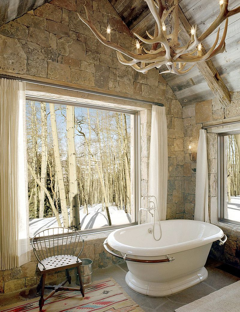 Rustic bathroom with stone wall, vintage bathtub and antler chandelier [Design: JLF & Associates]