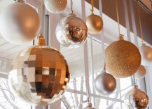 Silver and gold glass ball ornaments hung from matching ribbon in window
