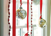 Silver and gold glass ball ornaments hung from red ribbon in a window