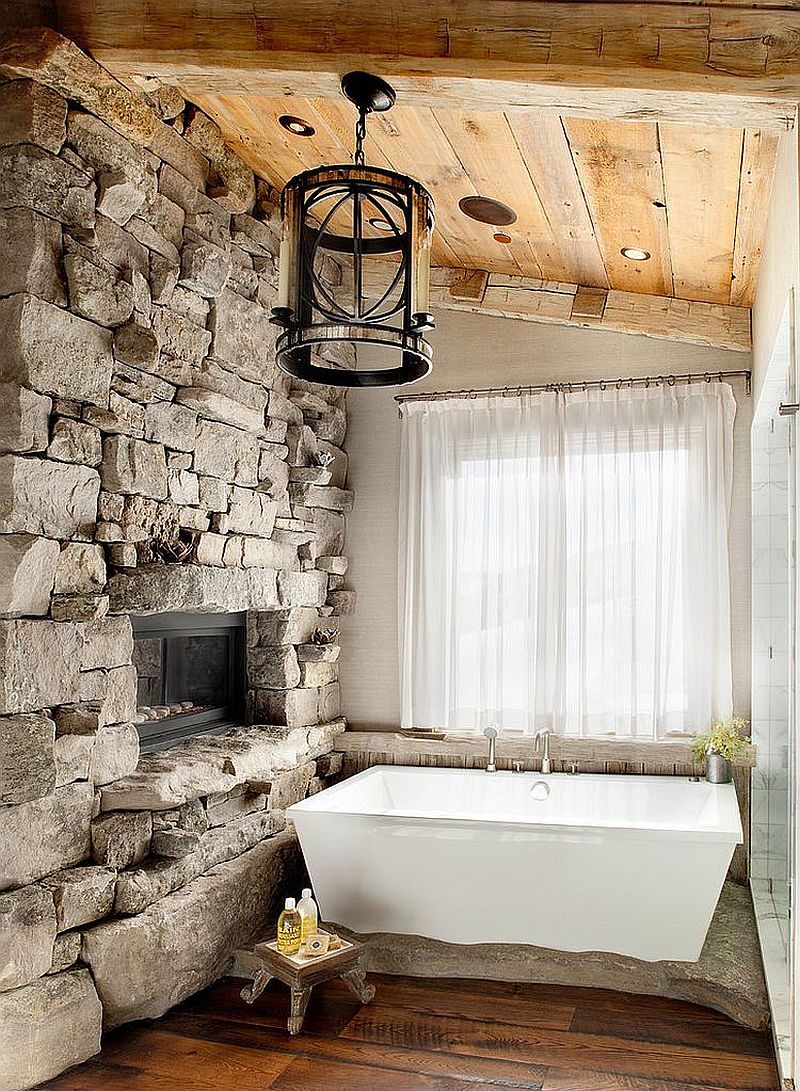 Ski lodge-inspired rustic bathroom with a stone wall and sheer curtains