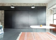 Sliding panels in black hide the kitchen