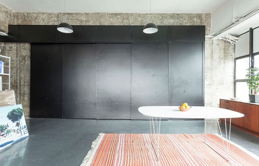 Sliding panels in black hide the kitchen