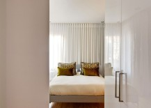 Small bedroom design with platform bed and white sheer curtains