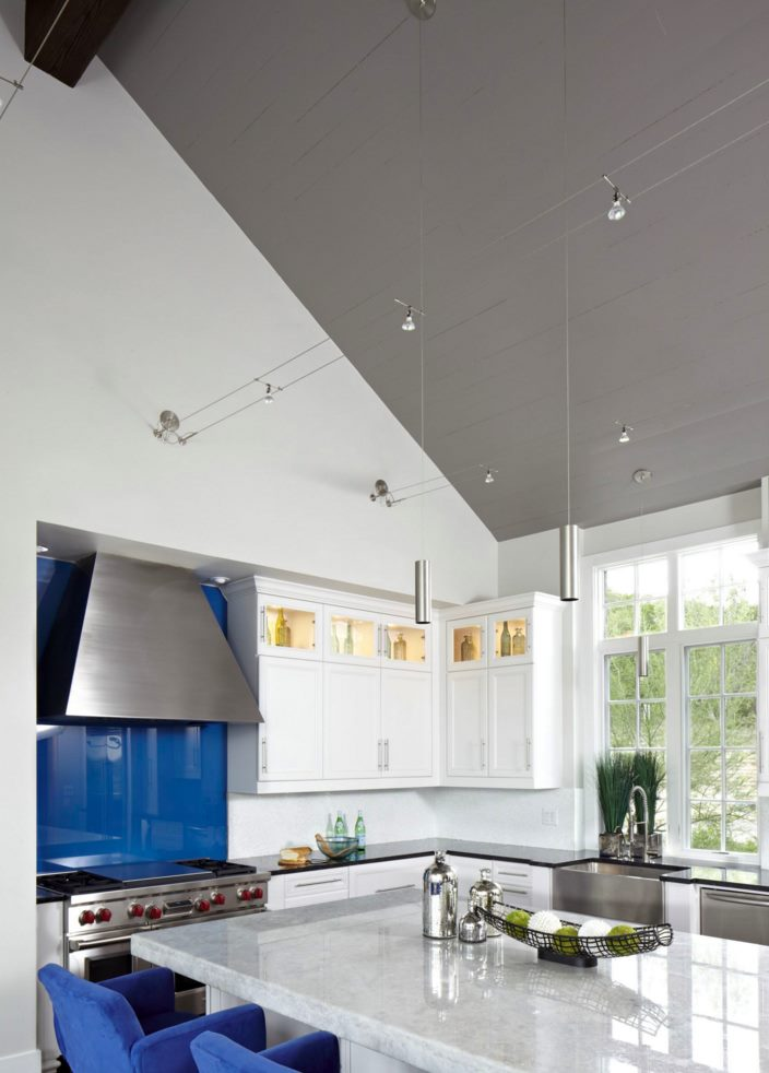 Small cylindrical pendants in a kitchen with blue accents