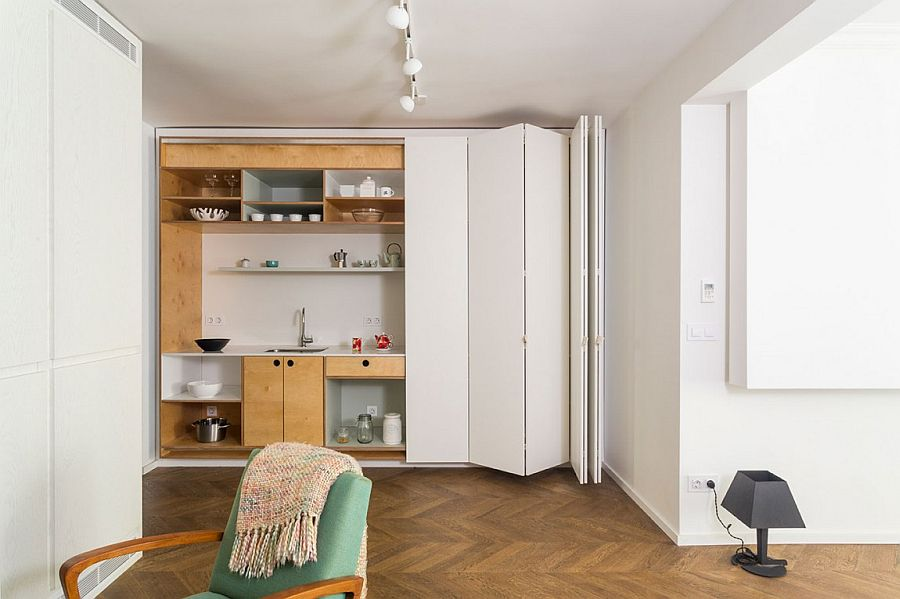 Stackable, folding white doors hide the kitchen when not in use