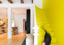 Staircase in yellow and penny tiled flooring delineate space inside the vivacious, remodeled row house
