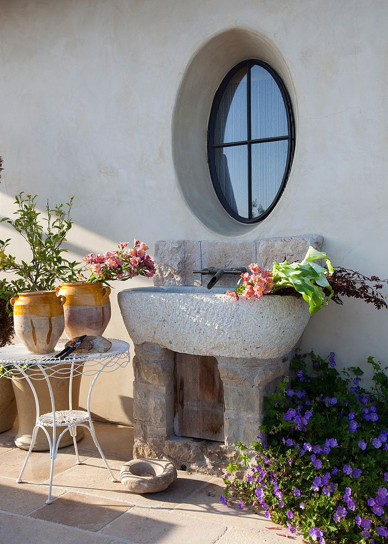 Stone sink in the patio adds to the Mediterranean style of the exterior