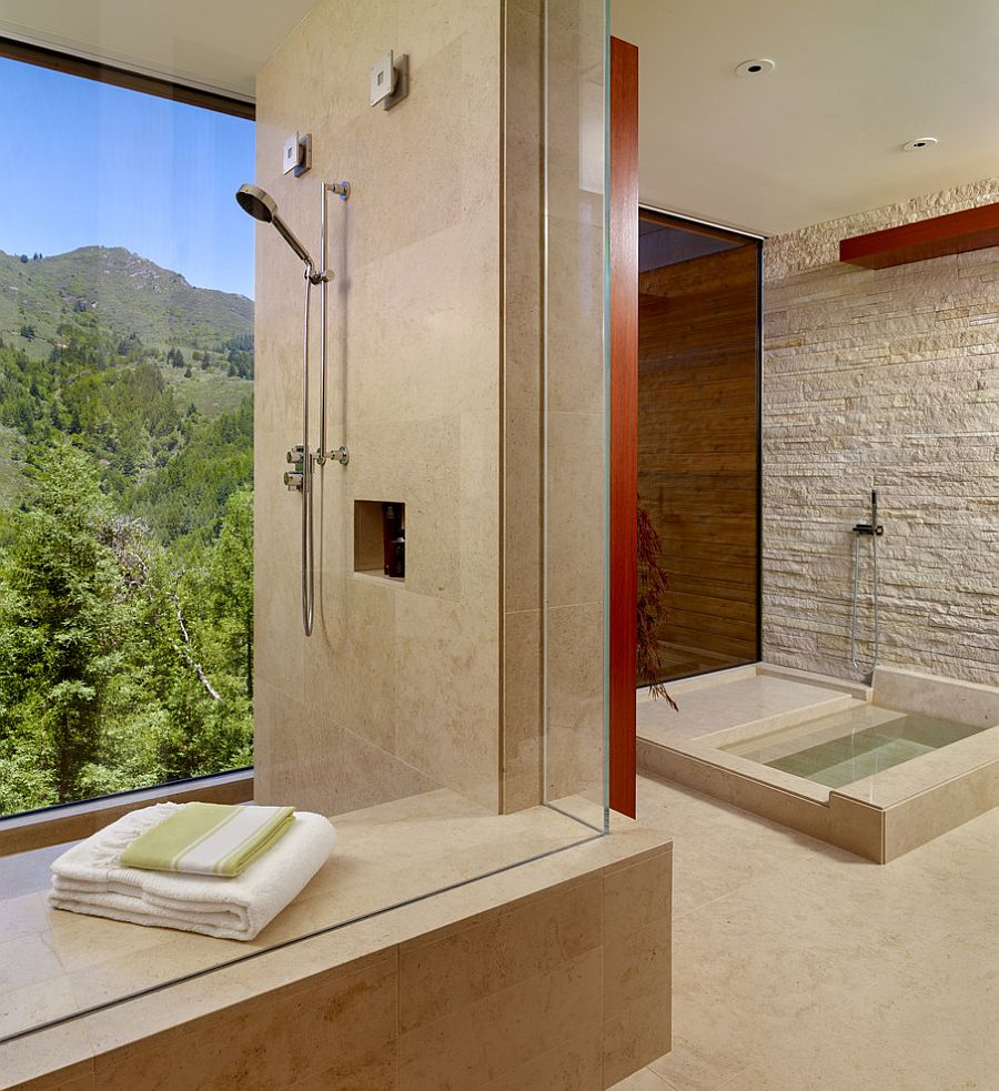 Stone wall brings a rougher texture to the refined contemporary bathroom [Design: C Wright Design]