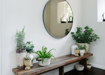 Stunning entryway setup with rustic bench, round mirror, and lots of plants