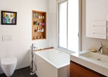 Tiny bathtub with a built-in wooden shelf next to it for bathroom accessories