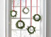 Tiny wreaths hung with red ribbon in a window