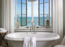 Vintage freestanding bathtub next to the window with sea view in beautiful beach style bathroom