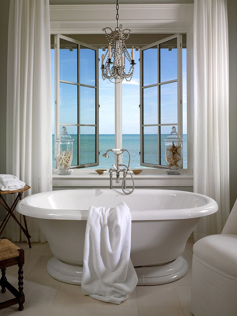 Vintage freestanding bathtub next to the window with sea view in a beautiful beach style bathroom [Design: Jill Shevlin Design]