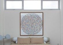 Wall art adds color to the small bedroom in white
