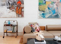Wall art and accent pillows add color and pattern to the simple brick wall backdrop in white