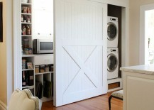 White barn doors to hide laundry appliances and other storage 217x155 15 Laundry Spaces That Cleverly Conceal Their Unsightly Appliances