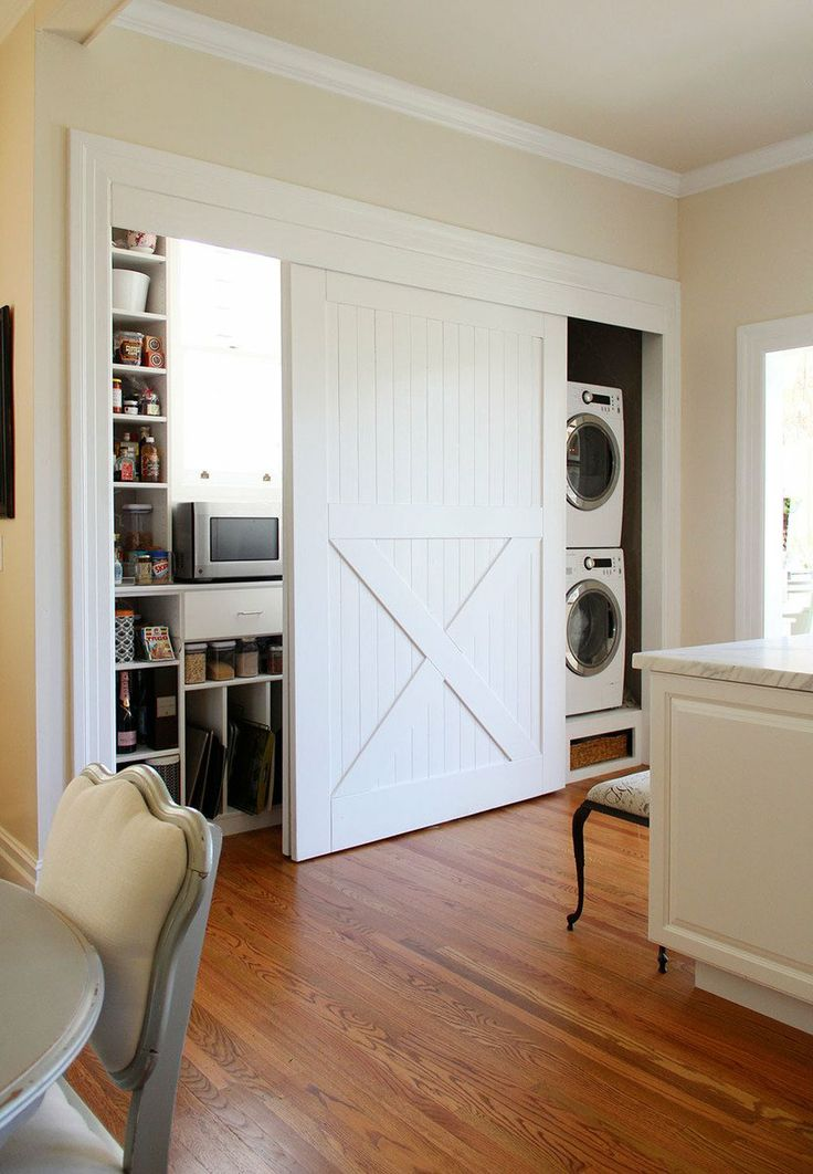 White barn doors to hide laundry appliances and other storage