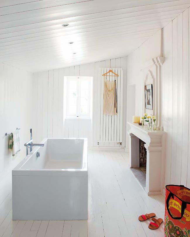 White bathroom and freestanding tub with fireplace