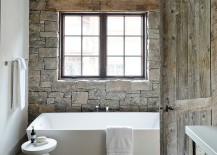 White standalone bathtub with Martini side table and a stone accent wall in the bathroom