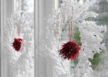 Wintery white and red wreaths hung in windows