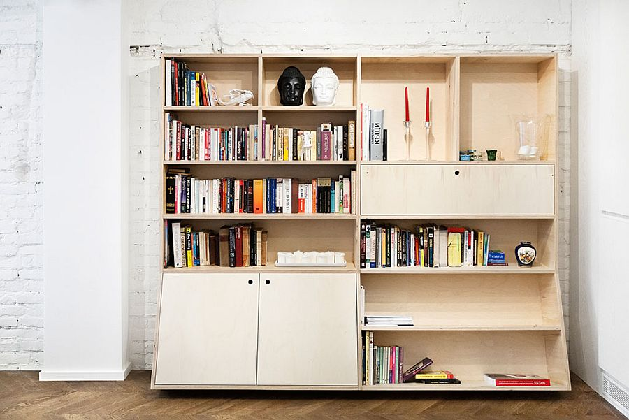 Wooden bookcase set against the exposed brick wall in the open plan living area