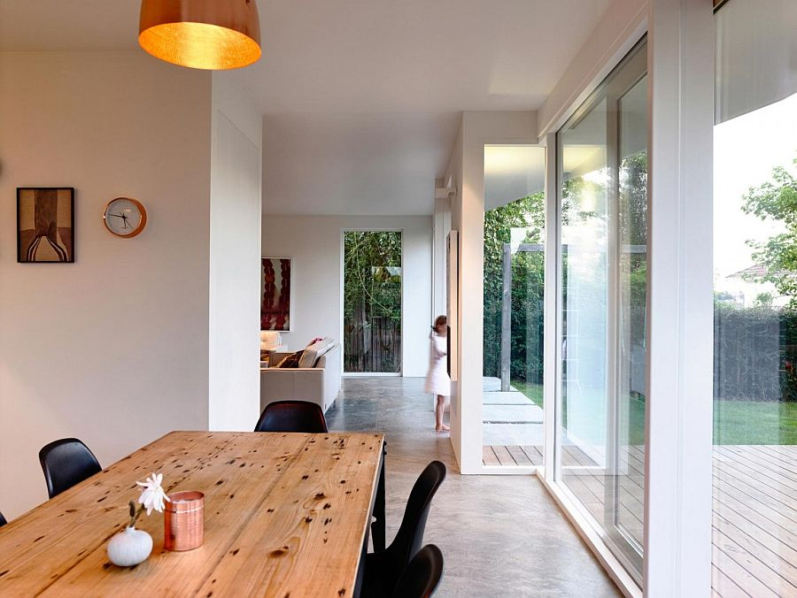 Wooden dining table and black chairs create a room within the kitchen with ease
