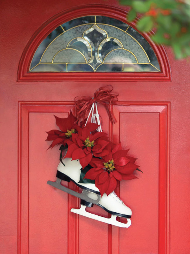 A pair of skates with some festive poinsettias hangs on a red door