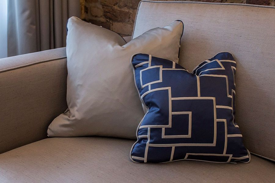 Accent piilows and couch in the living room enhance the blue-gray color scheme of the apartment