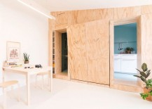 Active doors and wooden walls hide the kitchen, bed and other spaces
