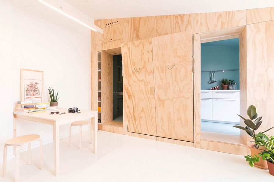 View in gallery Active doors and wooden walls hide the kitchen, bed and  other spaces