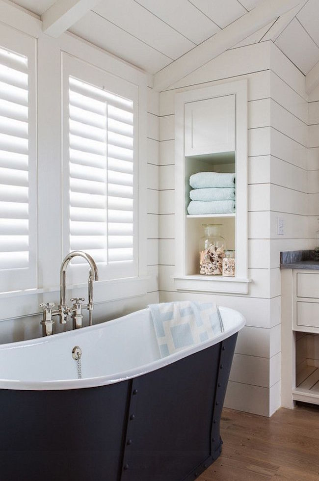 bathroom with shiplap walls and built in storage shelving near