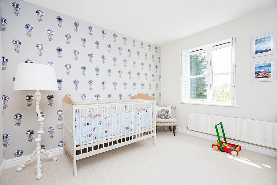 Beach style nursery in white with wallpaper that carries air balloon motif [Design: Elena Romanova Interiors]