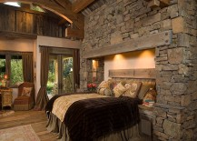 Bed built into a wall of rock and stone for a unique rustic bedroom