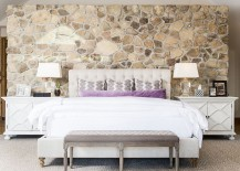 Bedside tables bring symmetry to the contemporary bedroom with stone wall
