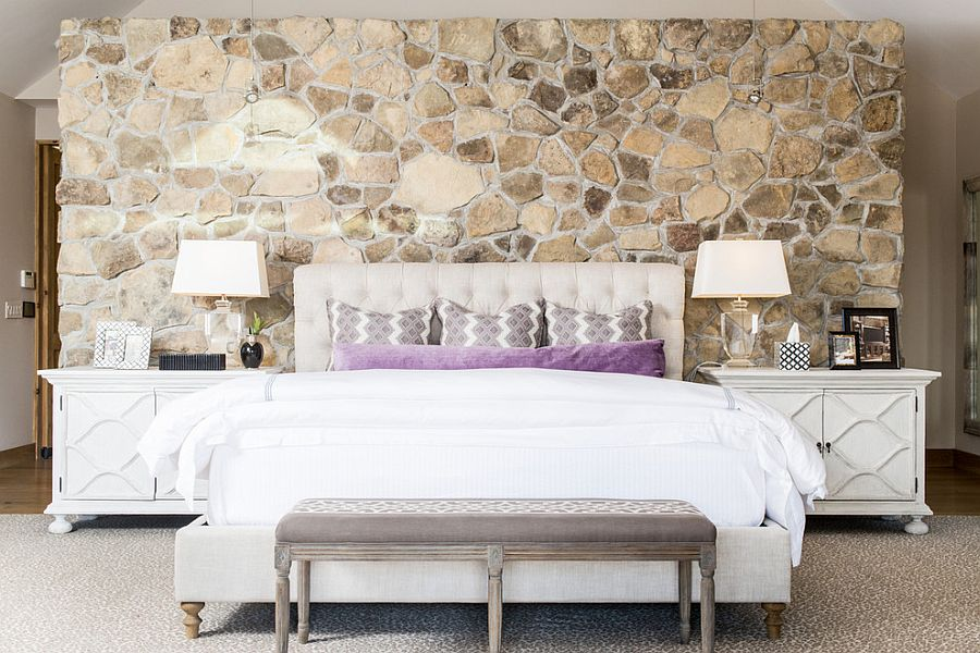 Bedside tables bring symmetry to the contemporary bedroom with stone wall [Design: Cashmere Interior]