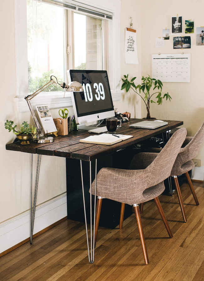 Bright office space with wood desk and touches of greenery