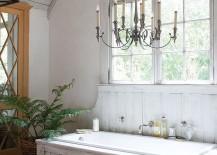 Classic chandelier, unique bathtub and farmhouse charm shape a relaxing bathroom
