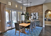 Color and pattern of the rug enliven the exposed brick wall dining room [Design: Maxim Lighting International]