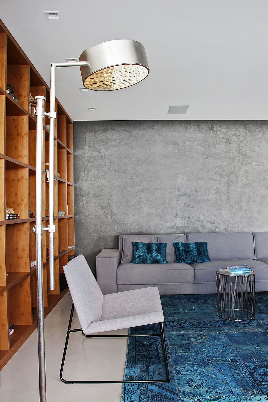 Contemporary couch in gray blends into the cement wall backdrop
