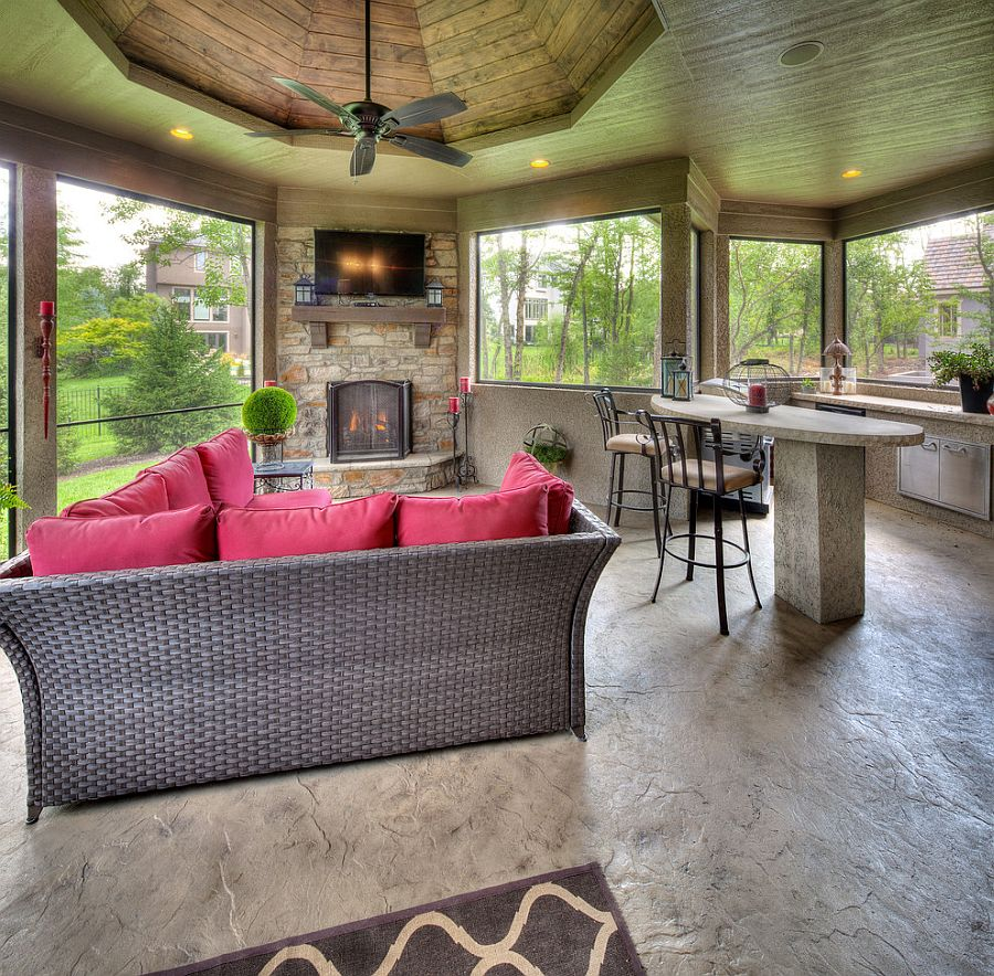 Cozy sunroom with fireplace, plush couch, innovative ceiling design and TV [Design: Starr Homes]