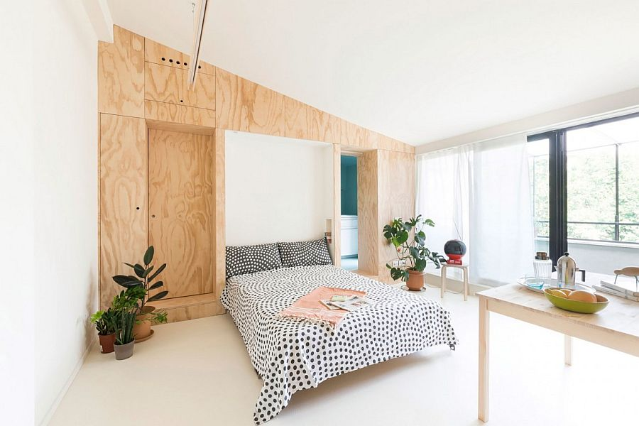 Custom plywood wall unit hides bathroom murphy bed and kitchen Tiny 28 Sqm Flat in Milan Wows with Flexible, Space Saving Design