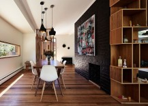 Dark accent brick wall fashions a dramatic focal point inside the contemporary dining space