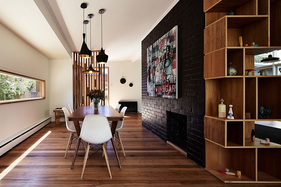 Dark accent brick wall fashions a dramatic focal point inside the contemporary dining space [Design: Maxa Design]