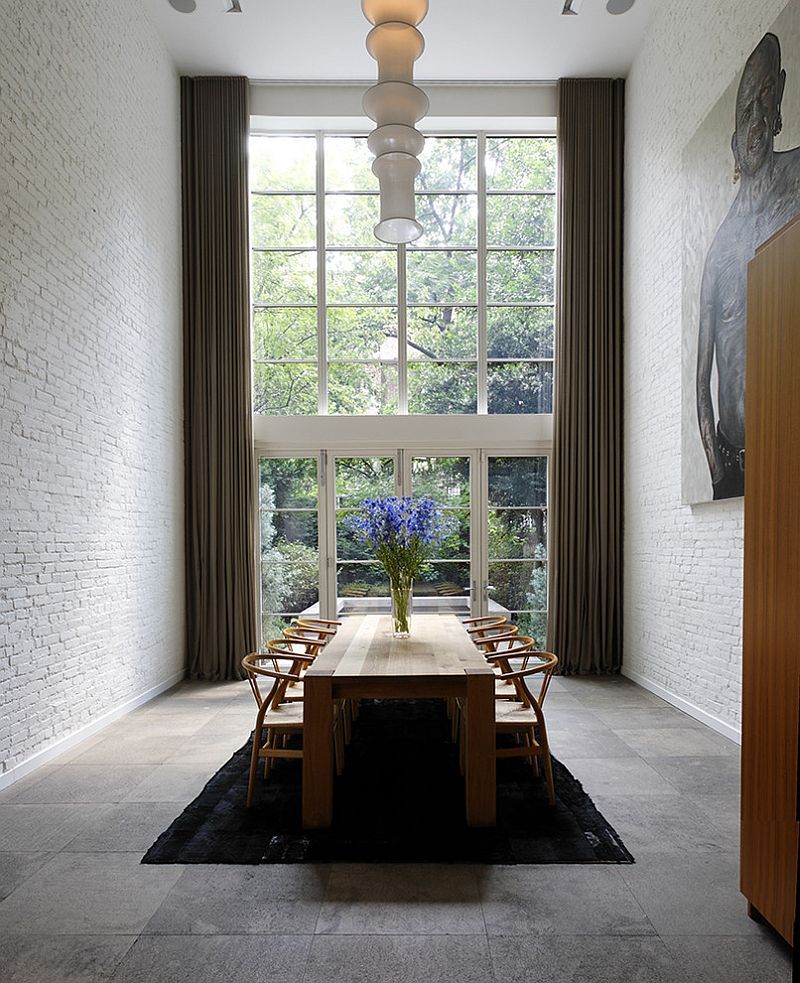 Dramatic double height dining room with brick walls and the classic Wishbone chair [Design: d'apostrophe design]