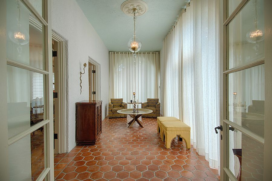 Drapes control the flood of sunlight as terracotta tiles bring Mediterranean elegance to the sunroom
