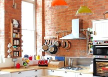 Eclectic kitchen with colorful lighting and brick wall backdrop [Design: Avocado Sweets Interior Design Studio]