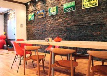 Eclectically vintage dining room with brick wall and a splash of color
