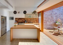 Elegant brick backsplash in the kitchen connects it visually with the courtyard outside [Design: Angus Mackenzie Architect]