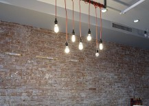 Exposed brick wall, lighting and wooden table for an industrial loft-inspired dining room