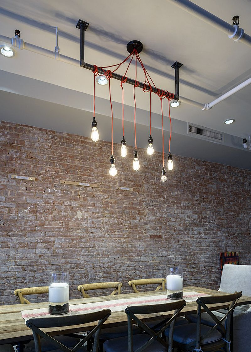Exposed brick wall, lighting and wooden table for an industrial loft-inspired dining room [Design: Jane Kim Design]